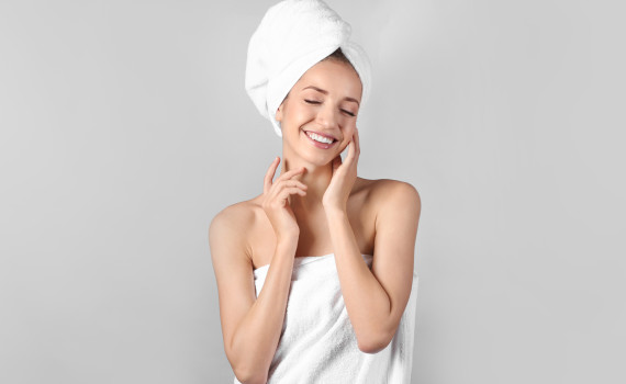 Young woman with soft skin after applying body cream, on light background