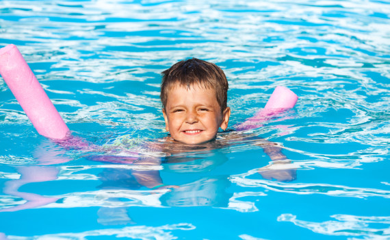 Happy small boy learns how to swim with pool noodle in swimming pool during summer
